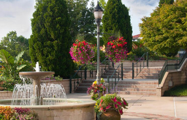 Colorful hanging flower baskets and pots around a fountain