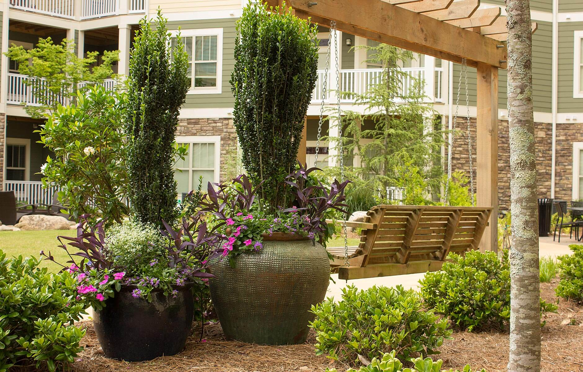 Landscaping enhanced with large flower pots full of spring colors