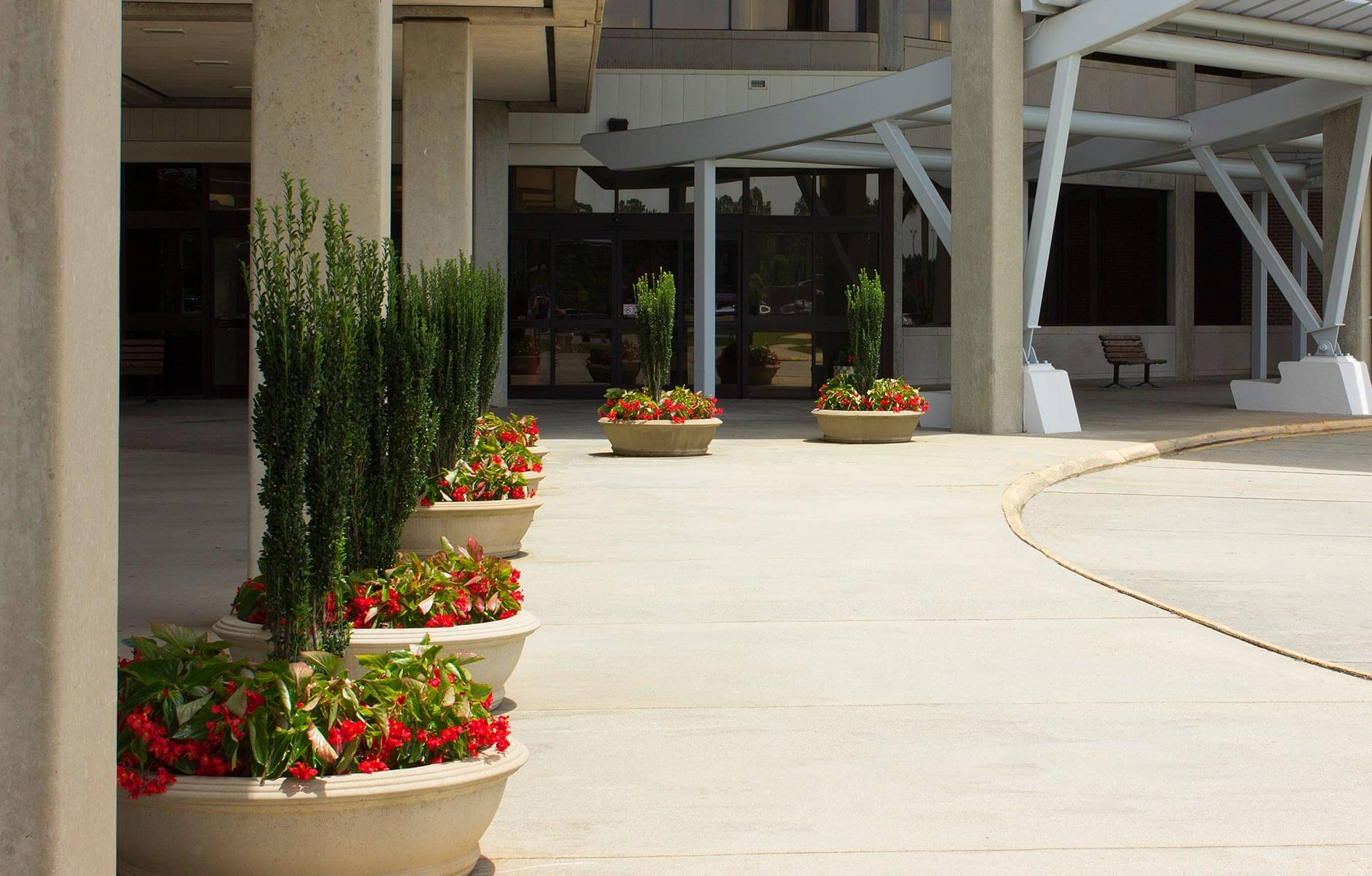 Large flower pots enhance the entrance to this industrial space