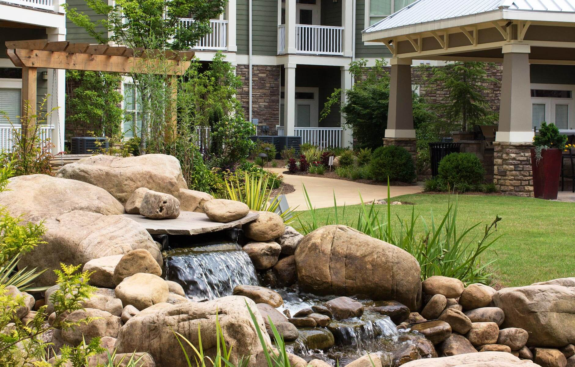 Green grass and a flowing fountain add charm to this multifamily property