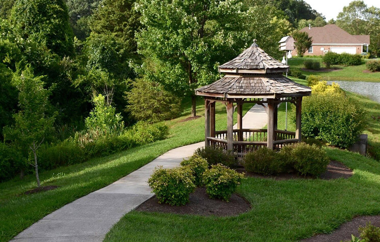 Lush green grass and a walkway around a pond at a property in Knoxville, Tennessee