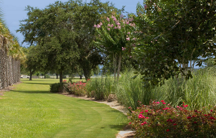 Neatly cut green grass and large flower bed at an industrial property in Mobile, Alabama