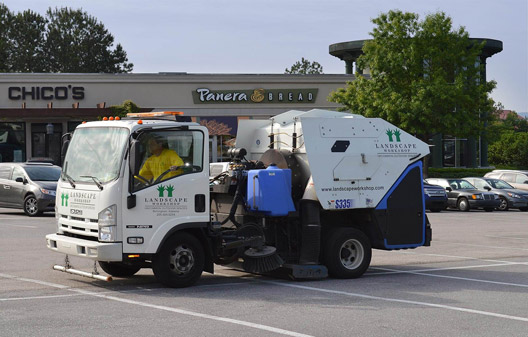 Power sweeping cleaning a parking lot at a retail property in Birmingham, Alabama